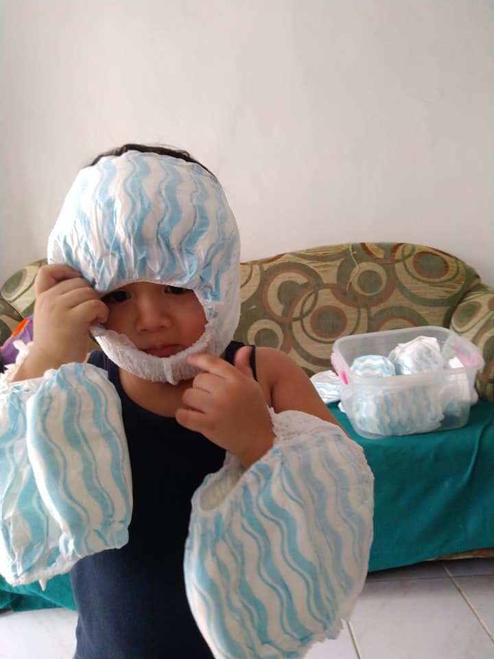 Toddler puts his diaper on his head as a costume
