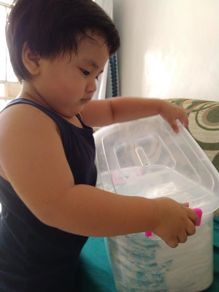 Toddler keeping his diapers in a box
