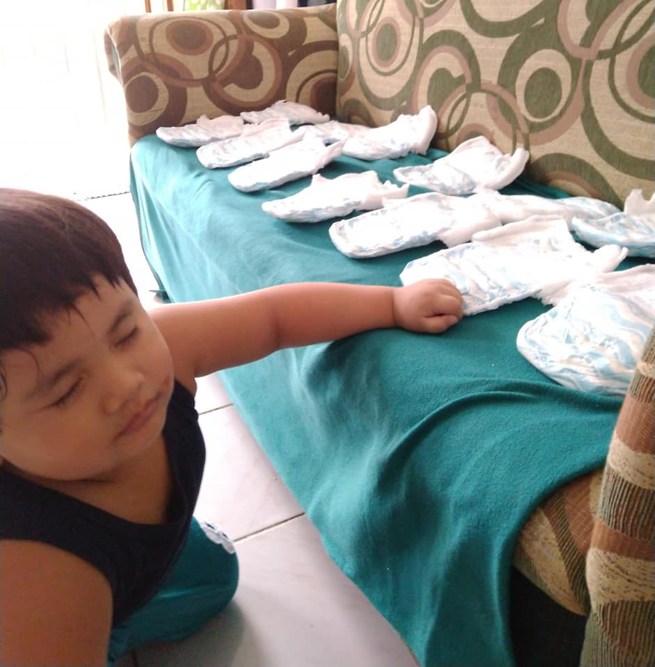 Toddler filing his diapers on the sofa
